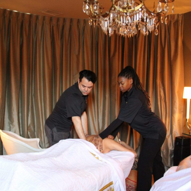 Two therapists working together to provide client with a four hands massage experience.
