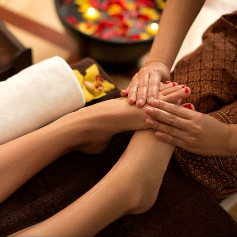 A therapist massaging a woman's feet with her hands.