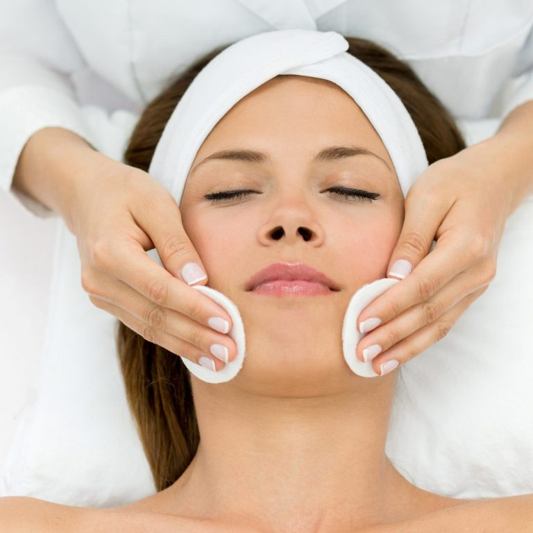 Specialist applying a cosmetic glycolic peel to a woman's facial skin.
