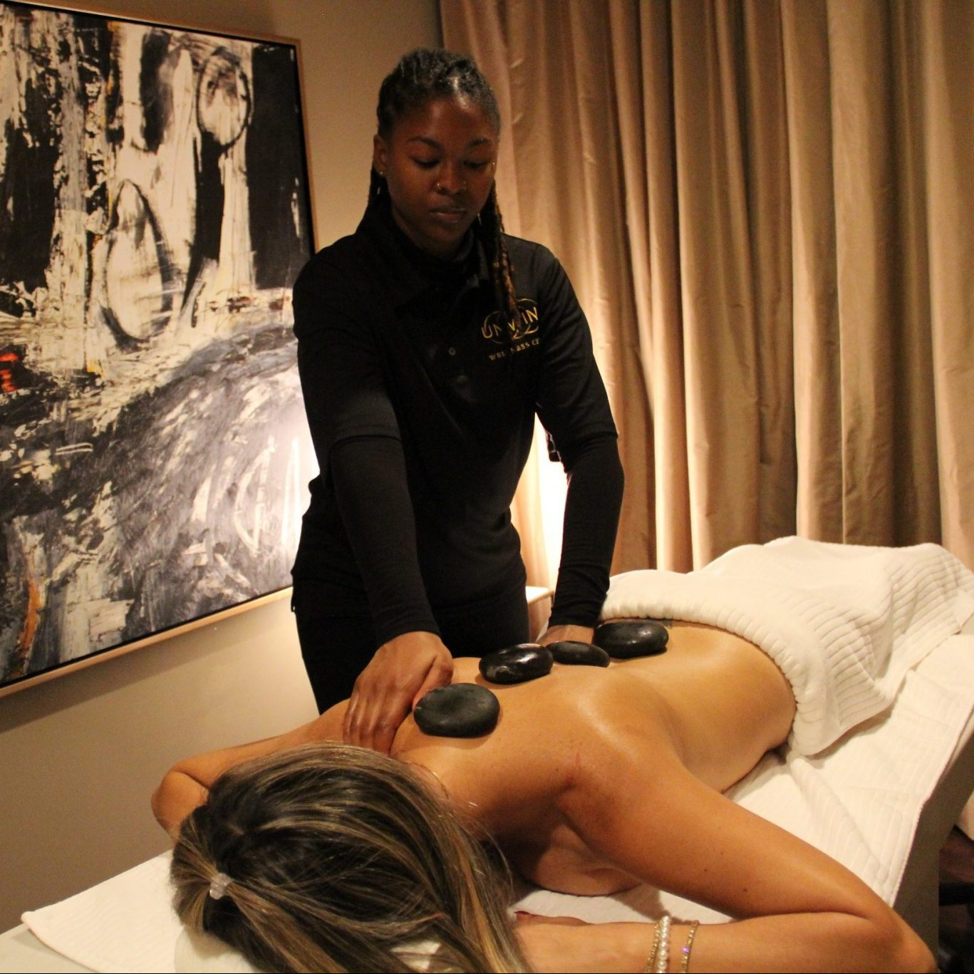 Massage therapist placing smooth, hot stones on a client's back to relieve tension.