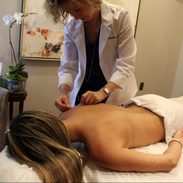 Woman receiving initial intake acupuncture session from specialist.