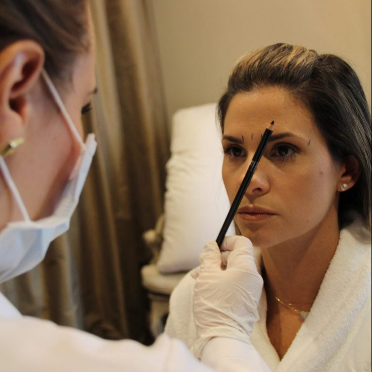 Woman receiving cosmetic facial work from a specialist.