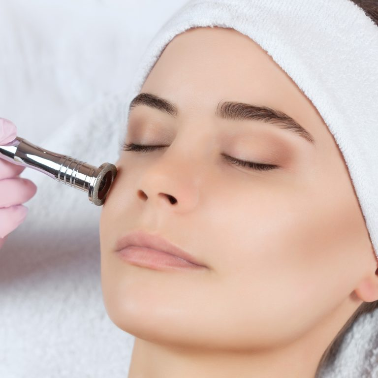 Specialist treating a woman's face with microdermabrasion instrument.
