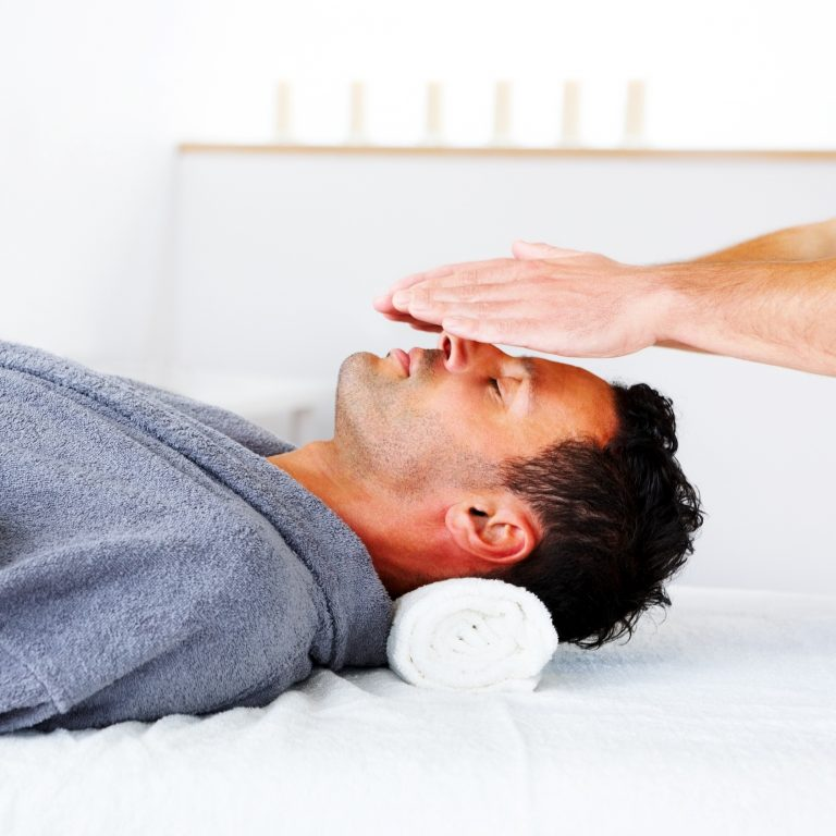 Man lying down while Reiki specialist moves hands above his body.