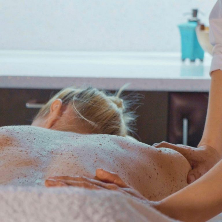 Woman having back layered and scrubbed with sugar by a therapist.