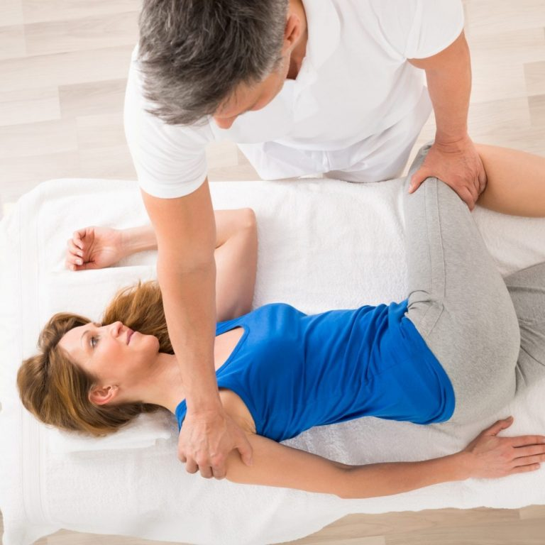 An athletic woman receiving a sports massage from a physical therapist.