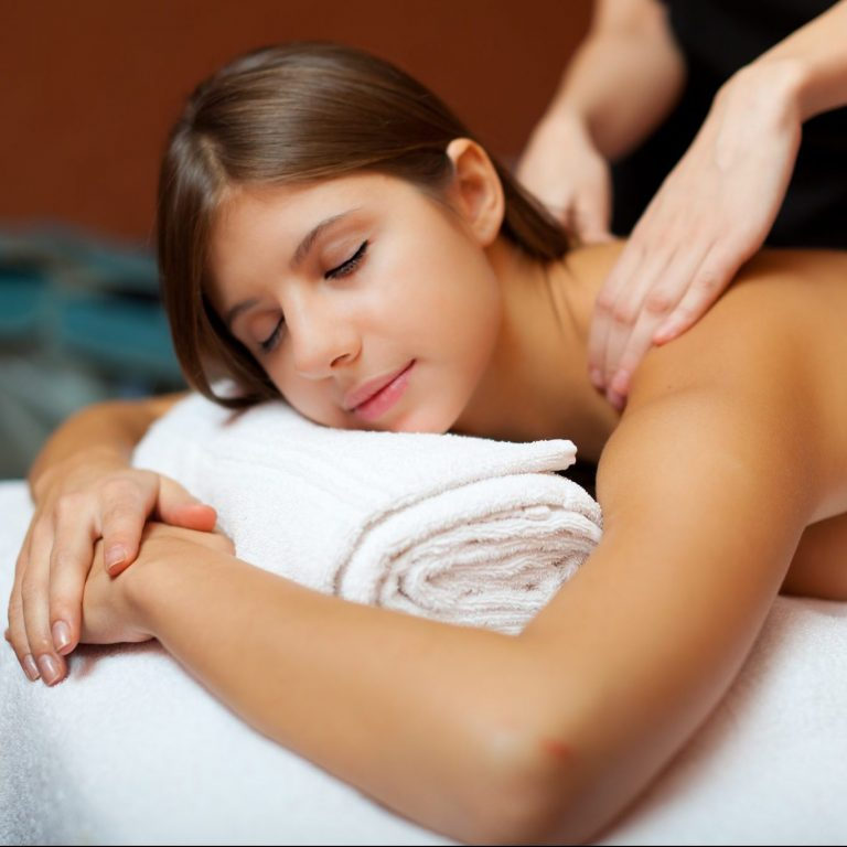 Woman experiencing a popular Swedish massage from a massage therapist.