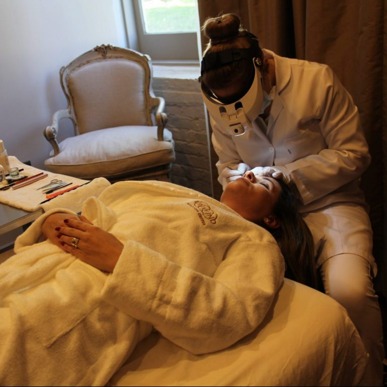 Woman receiving an exfoliating facial from a specialist.