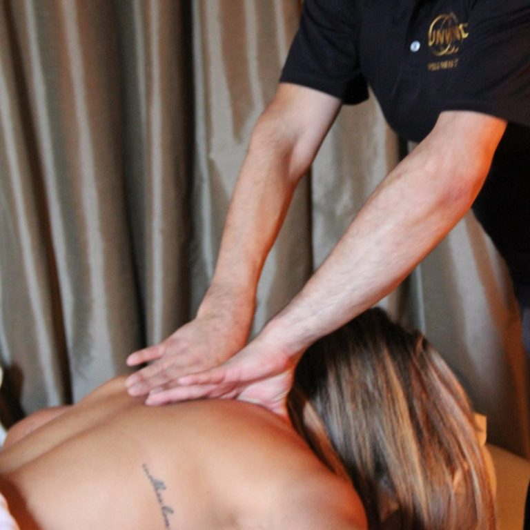 Massage therapist providing client with Unwind signature massage.