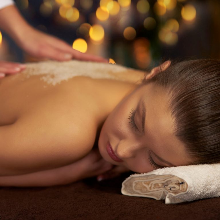 Resting woman having an exfoliating facial applied to her back.